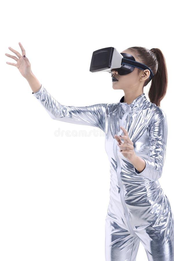 银色乳汁服装和VR耳机的美丽的少妇 图库摄影