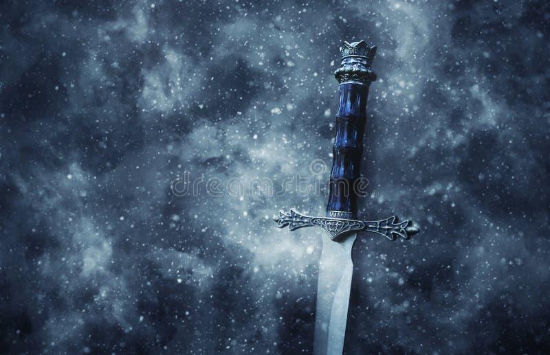 银色剑神奇和不可思议的照片在哥特式多雪的黑背景的 中世纪期间概念 库存照片