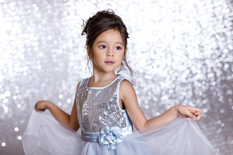 银色和蓝色礼服的逗人喜爱的微笑的小孩女孩 库存照片