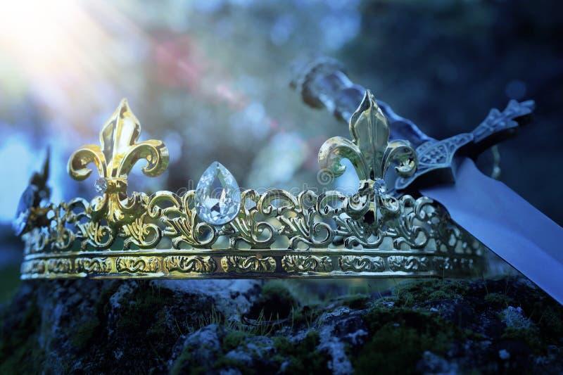 银色国王冠和剑神奇和不可思议的照片在用青苔盖的石头在英国森林或领域 库存图片
