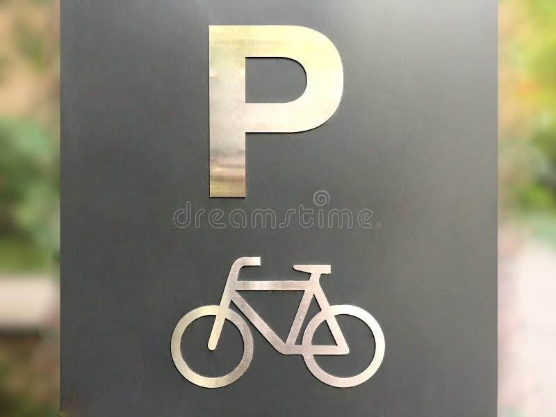 银色在灰色平台的自行车停放的标志在城市 免版税库存图片