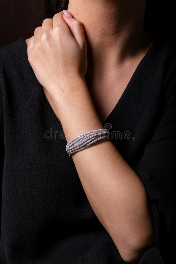 银色女性镯子在手边有在黑背景的金刚石的 免版税库存照片