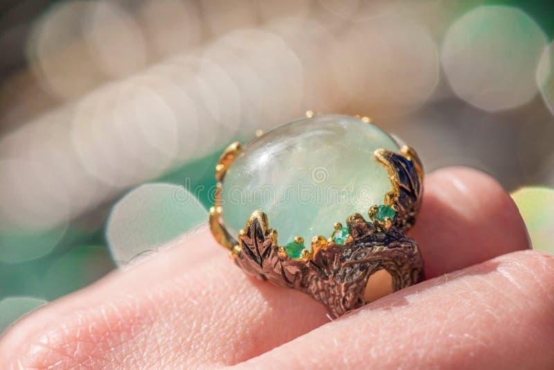 银色定婚戒指宏观射击在五颜六色,闪耀的背景的 免版税库存照片