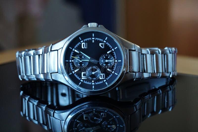 银色手表细节在午间以后,放置在黑垫 库存图片