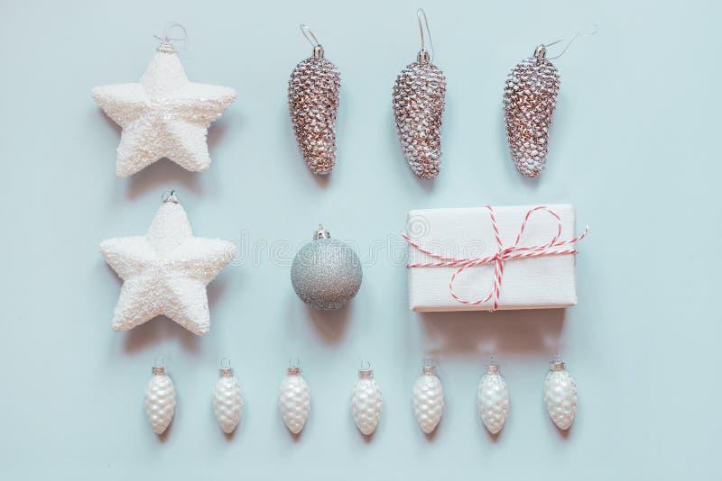 银色的圣诞节,装饰的白色装饰样式在淡色蓝色 最小的平的被放置的构成 库存图片