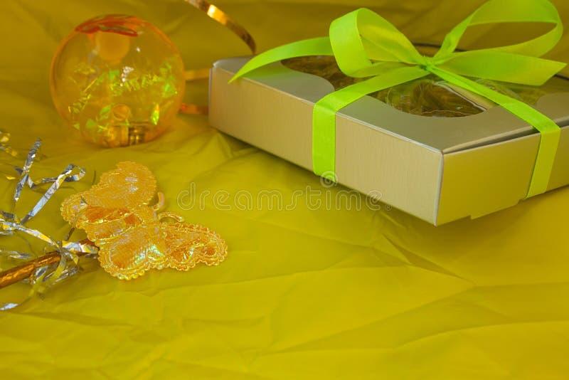 银色礼物盒栓了在黄色背景的黄色丝带弓 免版税图库摄影