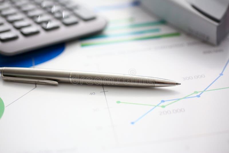 银色笔和计算器在准备好的工作场所使用 库存照片
