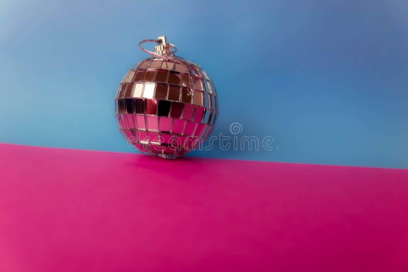 银色镜子音乐俱乐部迪斯科球xmas欢乐圣诞节球,在闪烁灰色桃红色紫色背景涂灰泥的圣诞节玩具 免版税库存图片