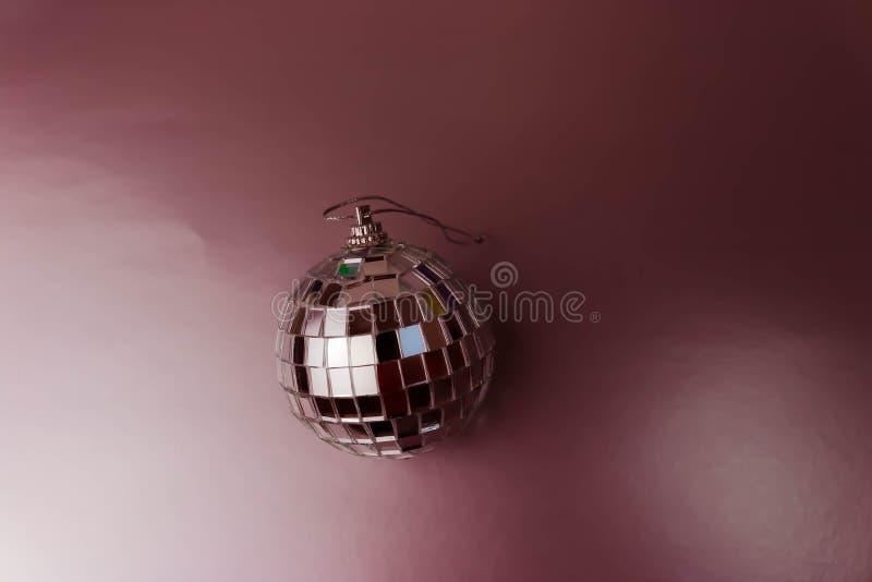 银色镜子音乐俱乐部迪斯科球xmas欢乐圣诞节球,在 yelow背景的闪闪发光涂灰泥的圣诞节玩具 库存图片