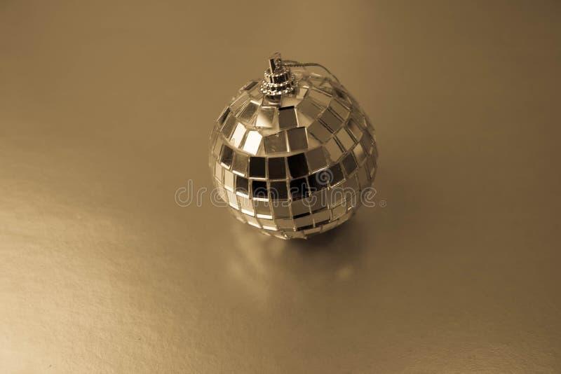 银色镜子音乐俱乐部迪斯科球xmas欢乐圣诞节球,在 yelow背景的闪闪发光涂灰泥的圣诞节玩具 免版税库存照片
