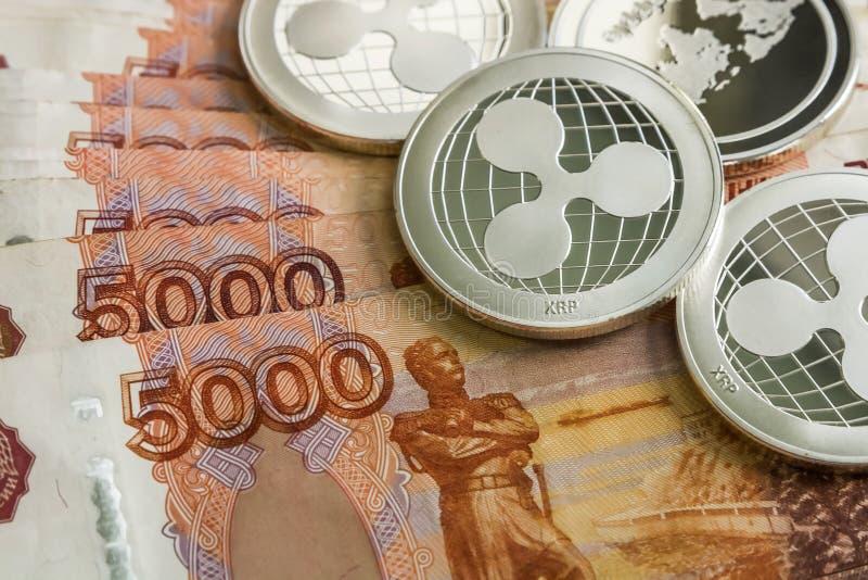 银色隐藏硬币起波纹XRP,俄罗斯卢布 金属硬币在光滑的背景中互相被计划,特写镜头 免版税库存照片