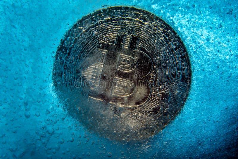 银色Bitcoin,在蓝色冰结冰的被咬住的硬币网上数字货币 块式链的概念,隐藏市场崩溃 ?? 库存图片