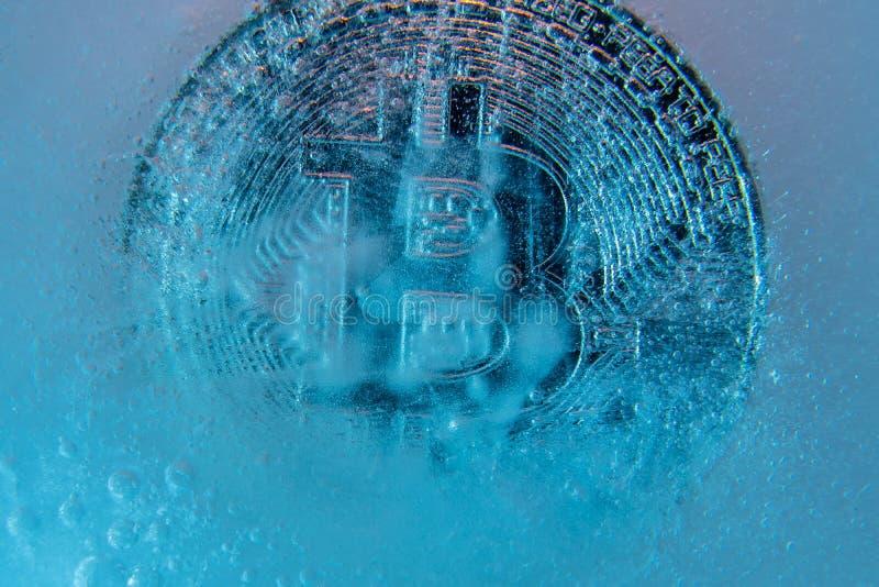 银色Bitcoin,在蓝色冰结冰的被咬住的硬币网上数字货币 块式链的概念,隐藏市场崩溃 ?? 免版税库存照片