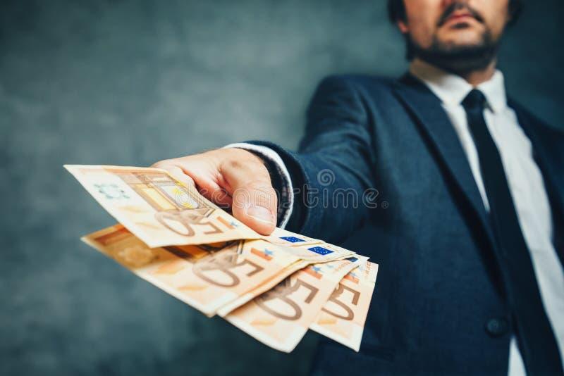 从银行提供的金钱贷款的商人在欧洲钞票 图库摄影