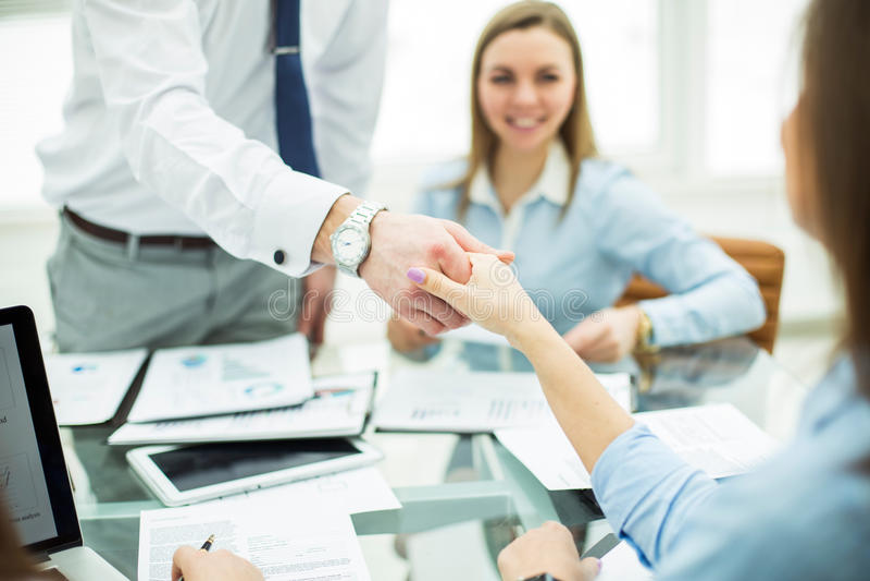 银行经理和顾客在签一个赚钱的合同以后握手 库存照片