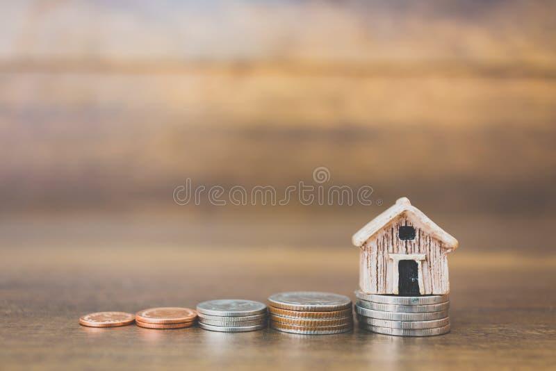 铸造在木背景的金钱和房子模型 免版税图库摄影