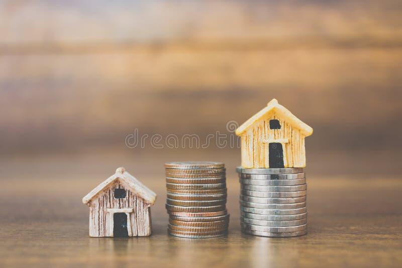 铸造在木背景的金钱和房子模型 免版税库存图片