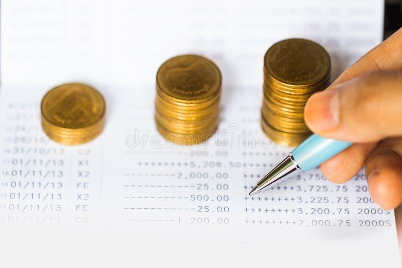 铸造堆和笔在银行存款簿背景 免版税库存图片
