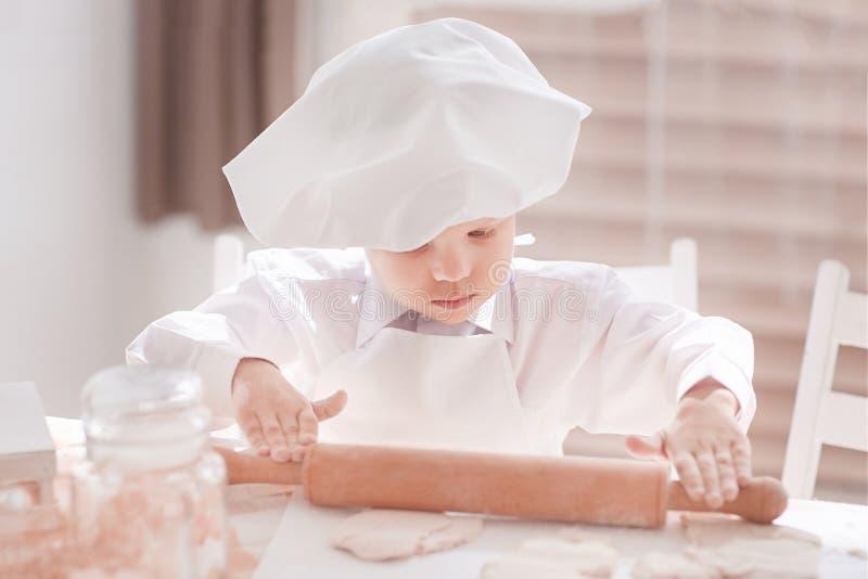 ?? 铺开面团的男孩厨师 免版税库存图片