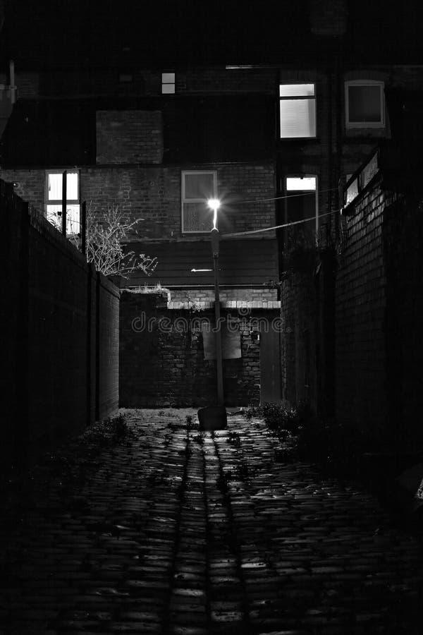 铺有鹅卵石卑劣与街灯在晚上 免版税图库摄影