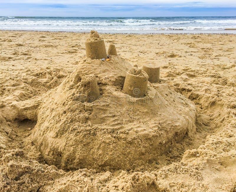 铺沙与塔的城堡大厦在海滩有在海的看法 免版税图库摄影