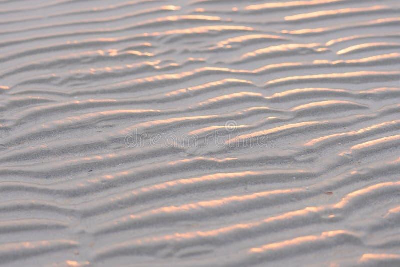 铺沙与日落的海滩和在沙子的自然波动图式在bea 库存照片