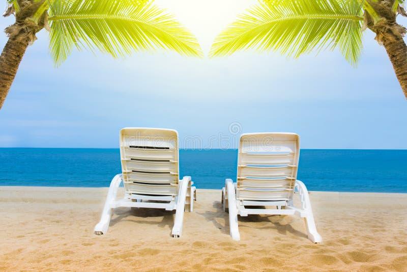 铺沙与椰子树的海滩与两把椅子和bokeh海滩热带背景、暑假和旅行想法,放松 库存照片