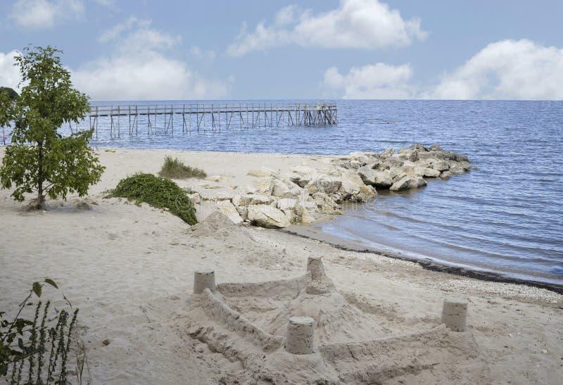 铺沙在一个海滩的城堡在有一个木码头的湖旁边在背景中 免版税图库摄影