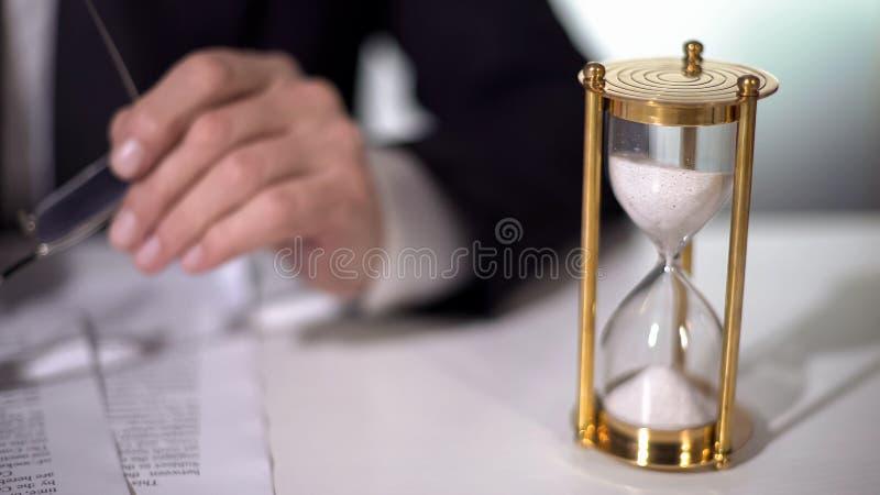 铺沙流动在签重要合同的商人,时间附近的时钟是金钱 免版税库存照片