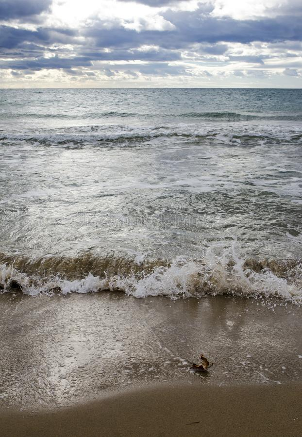 铺沙海滩有重的波浪和多云天空的mediteranean海 免版税库存照片