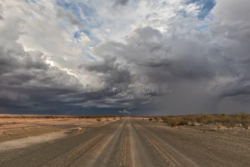 铺石渣有风雨如磐的天空的路,在途中到纳米比亚沙漠 Sossuvlei 库存照片