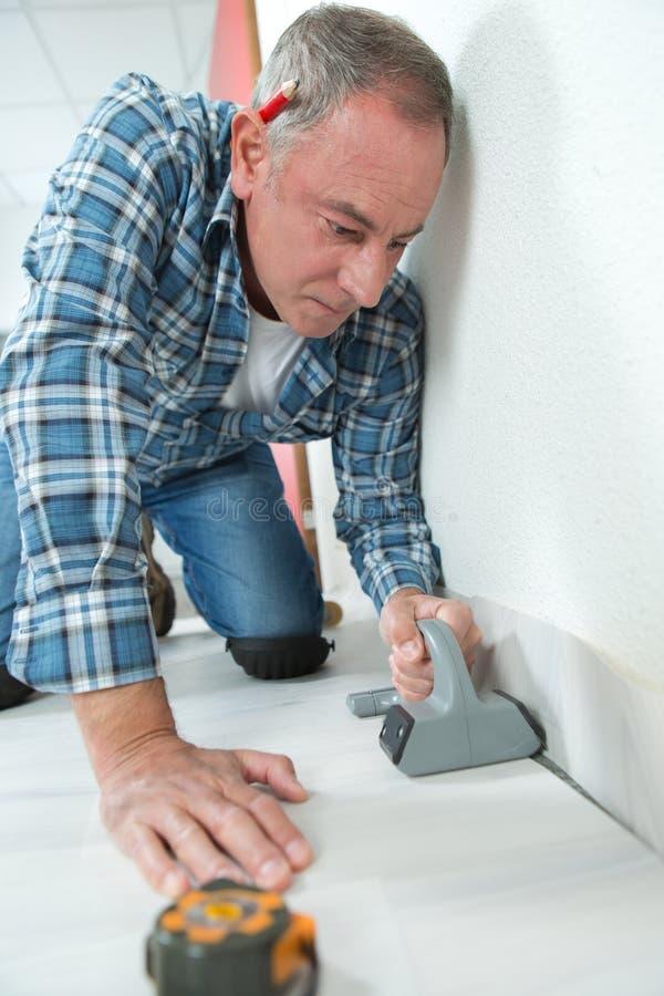铺磁砖工在地板设施时标记瓦片 免版税库存照片