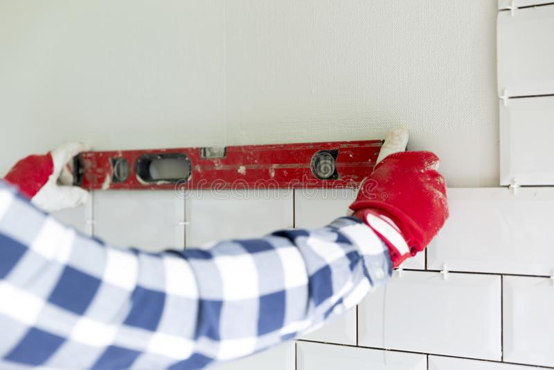 铺磁砖瓦片的过程在厨房里 承包商测量 免版税库存图片