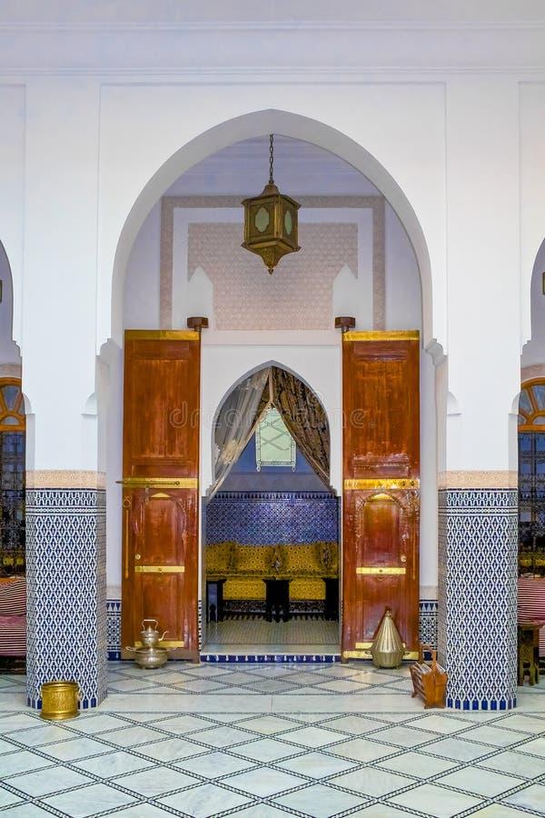 铺磁砖马赛克墙壁、摩尔人拱门和雪松被雕刻的门庭院 免版税图库摄影