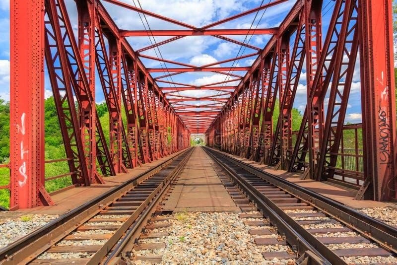 铺铁路在一座红色桥梁在夏日 库存照片