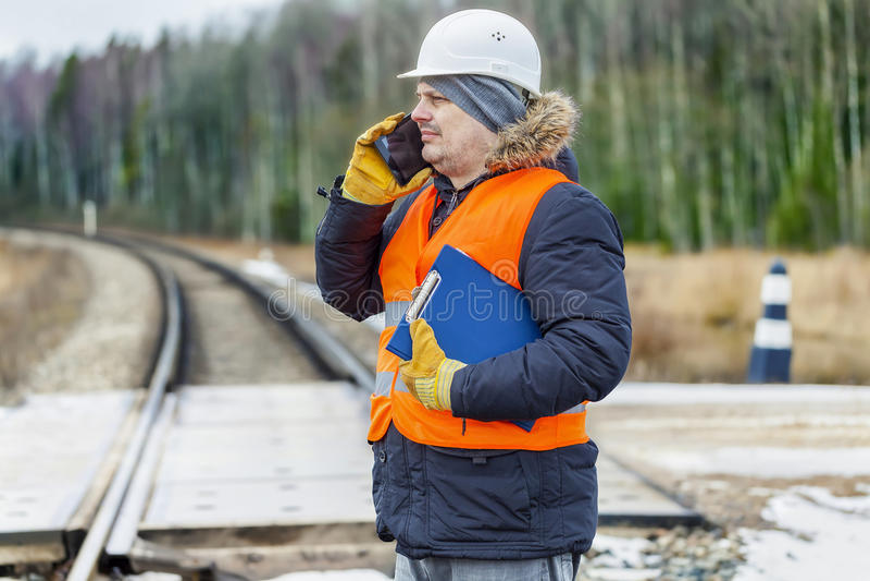 铺铁路有文献和smartp细磨刀石的工作者在铁路交叉 库存图片