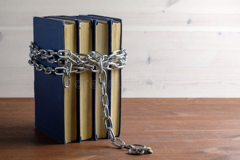 链子和书在分离轻和黑暗的背景的一张木桌上 免版税库存图片
