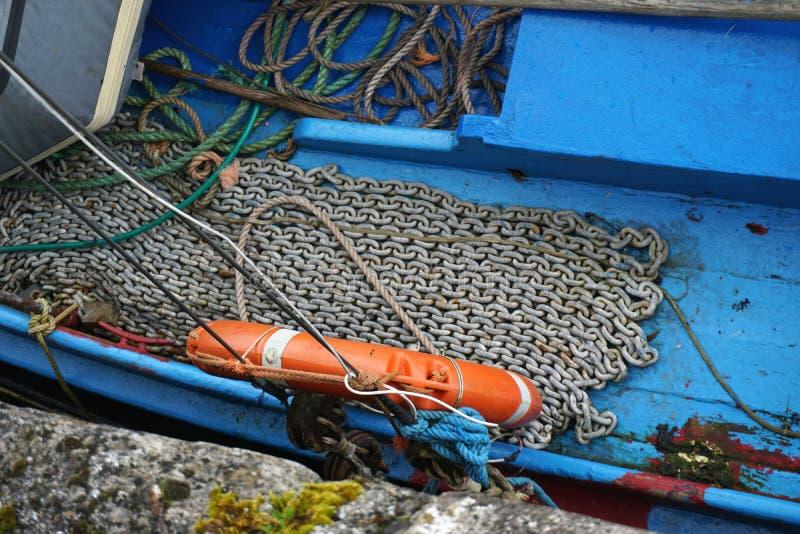 链子在小船的蓝色甲板整洁地放置了 免版税库存图片