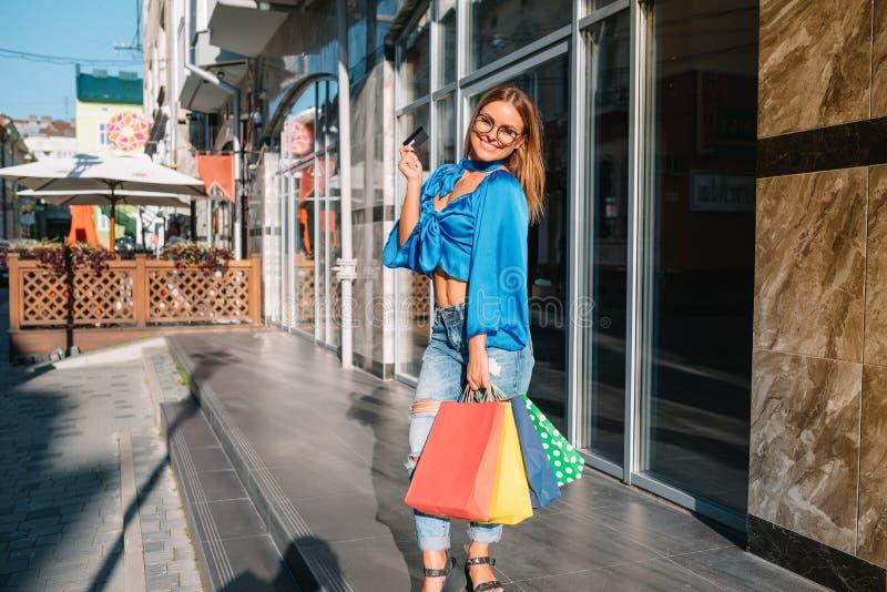 销售、消费主义、金钱和人的观念-在商场里拿着购物袋和信用卡的快乐年轻女性 库存照片