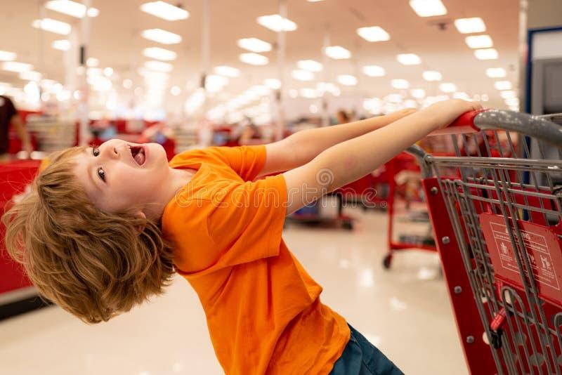 销售、消费主义和人的概念 — 儿童在杂货店购物车里吃东西 库存照片