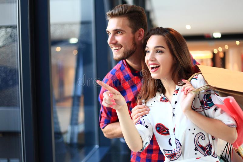 销售、消费者至上主义和人概念-愉快的年轻加上走在购物中心的购物袋 免版税图库摄影