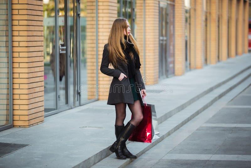 销售、消费者至上主义和人概念-拿着购物袋的愉快的年轻美丽的妇女,轻易地胜过商店 免版税图库摄影