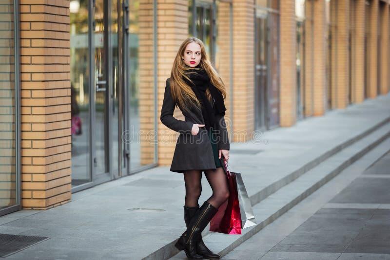 销售、消费者至上主义和人概念-拿着购物袋的愉快的年轻美丽的妇女,轻易地胜过商店 免版税库存照片
