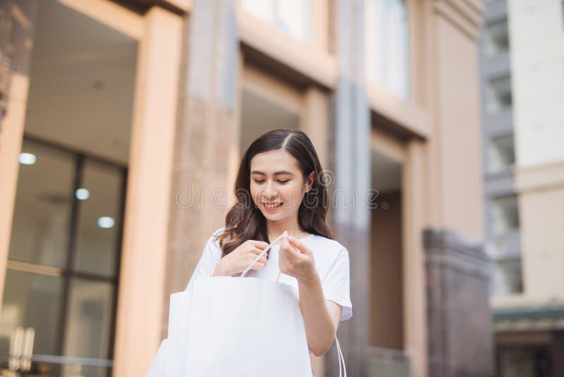 销售、购物、旅游业和愉快的人概念-有购物带来的美女在ctiy 免版税库存照片