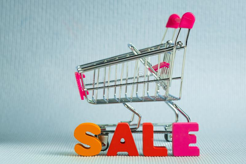 销售五颜六色的木文本和购物车或者超级市场拖钓 免版税库存照片