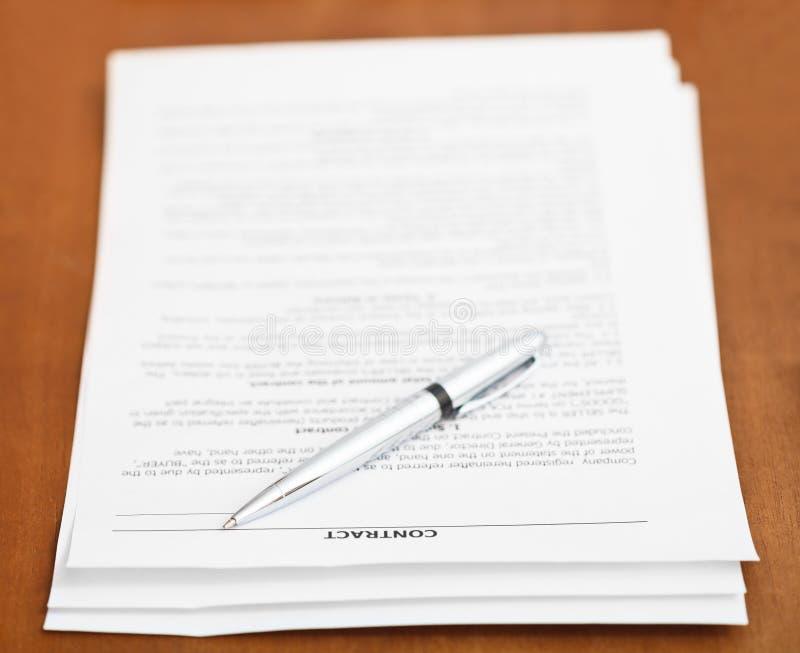 销售合约和银笔在木桌上 库存照片