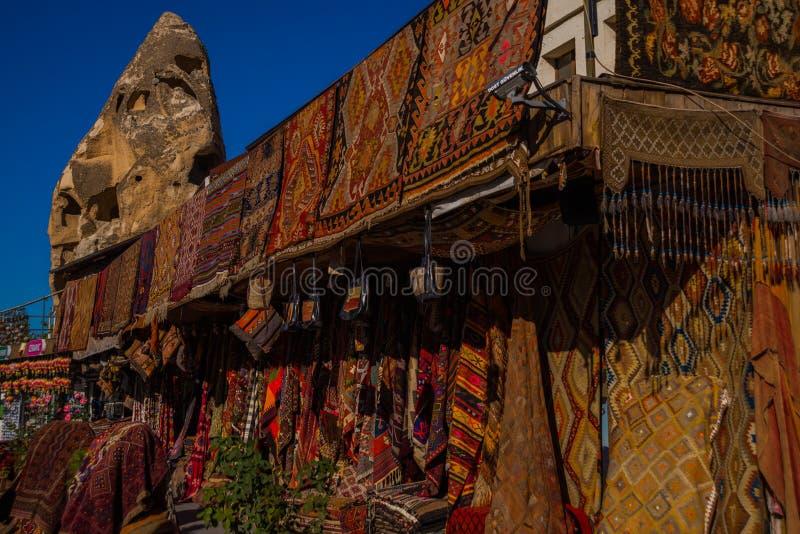 销售在市场上,在街道上的土耳其义卖市场,不同的地毯正面图在市场上在卡帕多细亚,土耳其 免版税库存照片