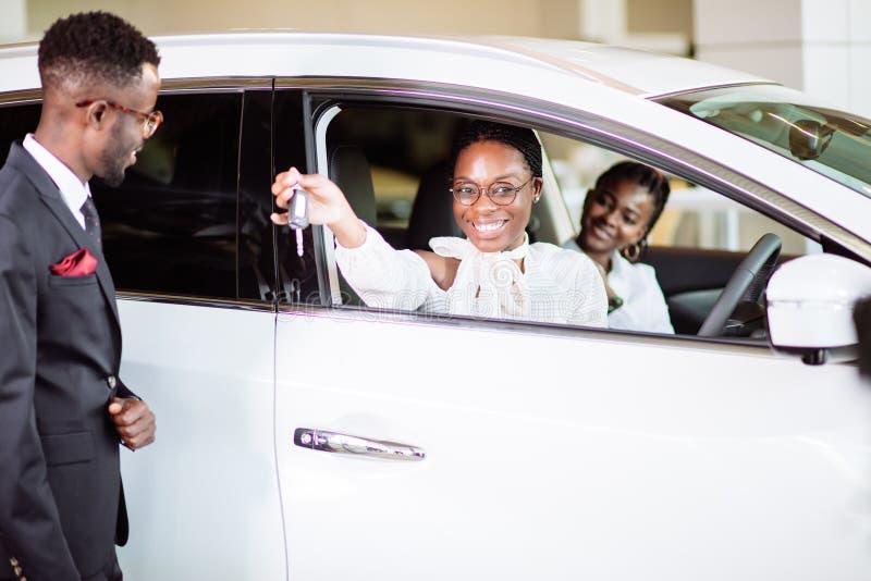 销售情况在售车行中,年轻非洲夫妇得到新的汽车的钥匙 免版税库存照片