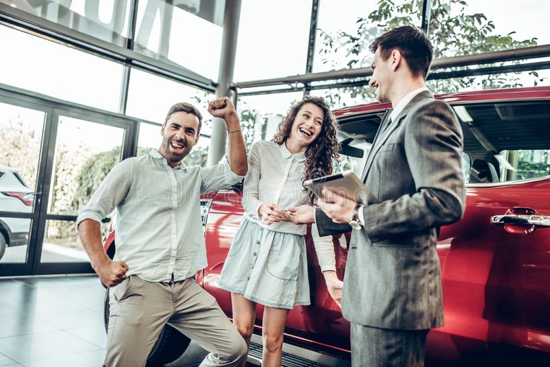 销售情况在售车行中,经销商递自动钥匙对一对年轻夫妇,他们被激发,站立在的汽车 免版税库存照片