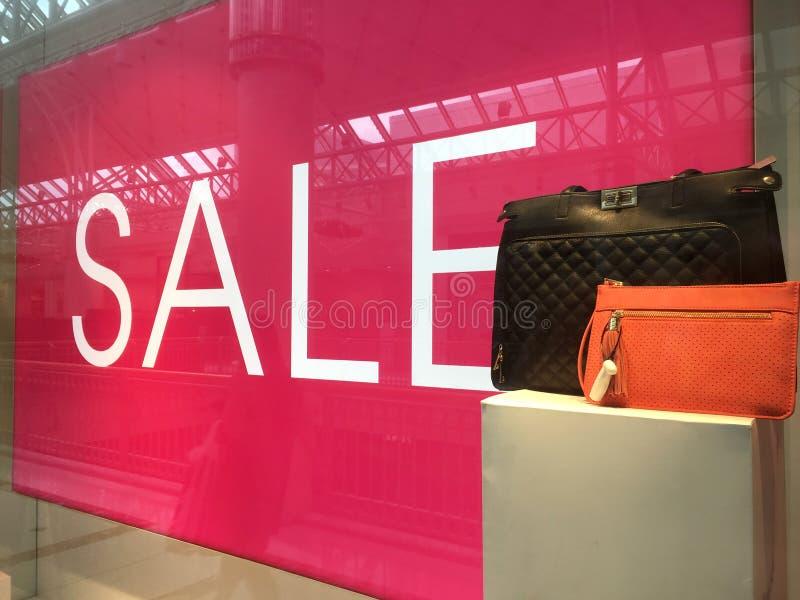 销售标志和提包在显示在商店前窗里 免版税库存图片